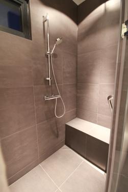 Douche met zitje en een handvat op een esthetische maar praktische plek.