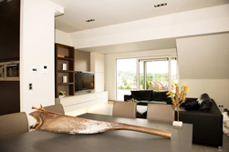 Door de keuken open te werken is er in de ruimte een luchtig geheel gecreëerd.<br />Het spel van de lichte en donkere meubels ontrafeld de keuken in aparte delen,<br />waardoor de focus op de witte lage meubels komt te liggen.<br />Uitvoering Alkas.