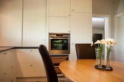 Licht klassieke keuken met vlakke MDF panelen met plankverdeling (V-groef) , afgewerkt met een structuurlak en met een gepolierd strak afgewerkt granieten tablet in Indian Black(zwart) als contrast op de lichte lak kleur. Chemin de Fer trekkers op de deuren.