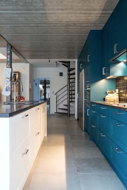 Grote keukenwand met eiland opgenomen in de leefruimte. Gans de wandkast is uitgevoerd in een gedurfde blauw-groene petroleumkleur met daartegenover het rustig witte eiland.