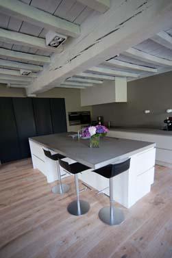 Heel strakke moderne keuken in een super rustiek interieur. De keuken is volledig greeploos, waarbij de lage kasten in structuurlak zijn uitgevoerd en de hoge kasten in een eik fineer dat donker is af gewerkt. Licht grijs composiet werkblad , opgedikt naar 6 cm wat de strakke look benadrukt.