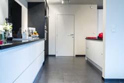 Super moderne greeploze keuken in een gelijkvloers (ietwat donker) appartement. Prachtig is hier het contrast tussen de witte lage kasten en de zwarte(met houtstructuur) hoge kasten in de lange wand. De open keuken hoort bij de ganse leefruimte en mag dus opvallend zijn, maar niet overheersend.
