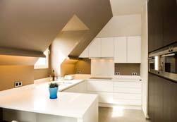 Inrichting van een loft te Lichtaart. De keuken is een modern, strak geheel geworden, gemaakt in 2 kleuren laminaat, hoogglans wit en wenge hout imitatie. Er is gekozen voor een wit composiet werkblad (Pure White Diresco) met een strakke voorkant. Het verlek is uitgefreesd en de onderbouw bakken zijn in RVS van Franke
