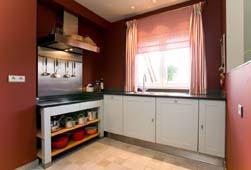Klassieke keuken, geïnspireerd op engelse stijl, met een open structuur onder de kookplaat en de kaderdeuren met vlak paneel en een structuur lakafwerking. De inox plint en het donker strakke granieten werkblad geven de moderne toets die nodig is om de link te leggen met de rest van het interieur in het appartement.