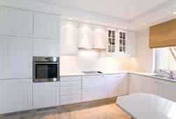 Licht klassieke keuken door de lichte kleuren die gekozen zijn voor de lak en het werkblad. Het klassieke karakter wordt wel ondersteund door de zandsteen ( Franse Bovilon) vloertegels en de moluur op de lichthemel tot aan het plafond.